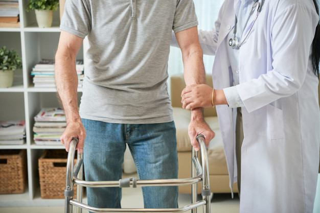 unrecognizable-female-doctor-helping-male-patient-walk-with-walking-frame_1098-20659