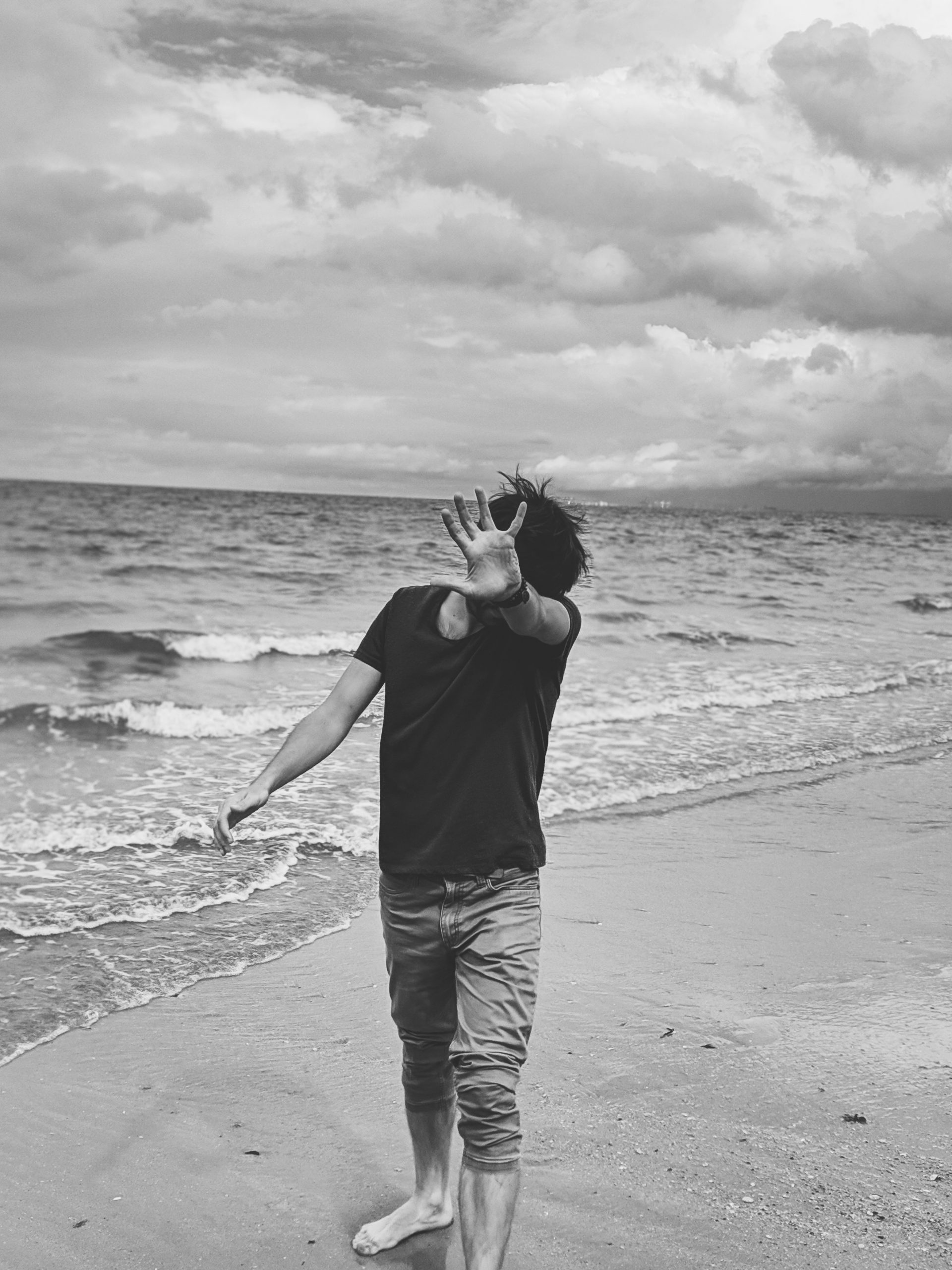 monochrome-photo-of-person-standing-on-seashore-2762839