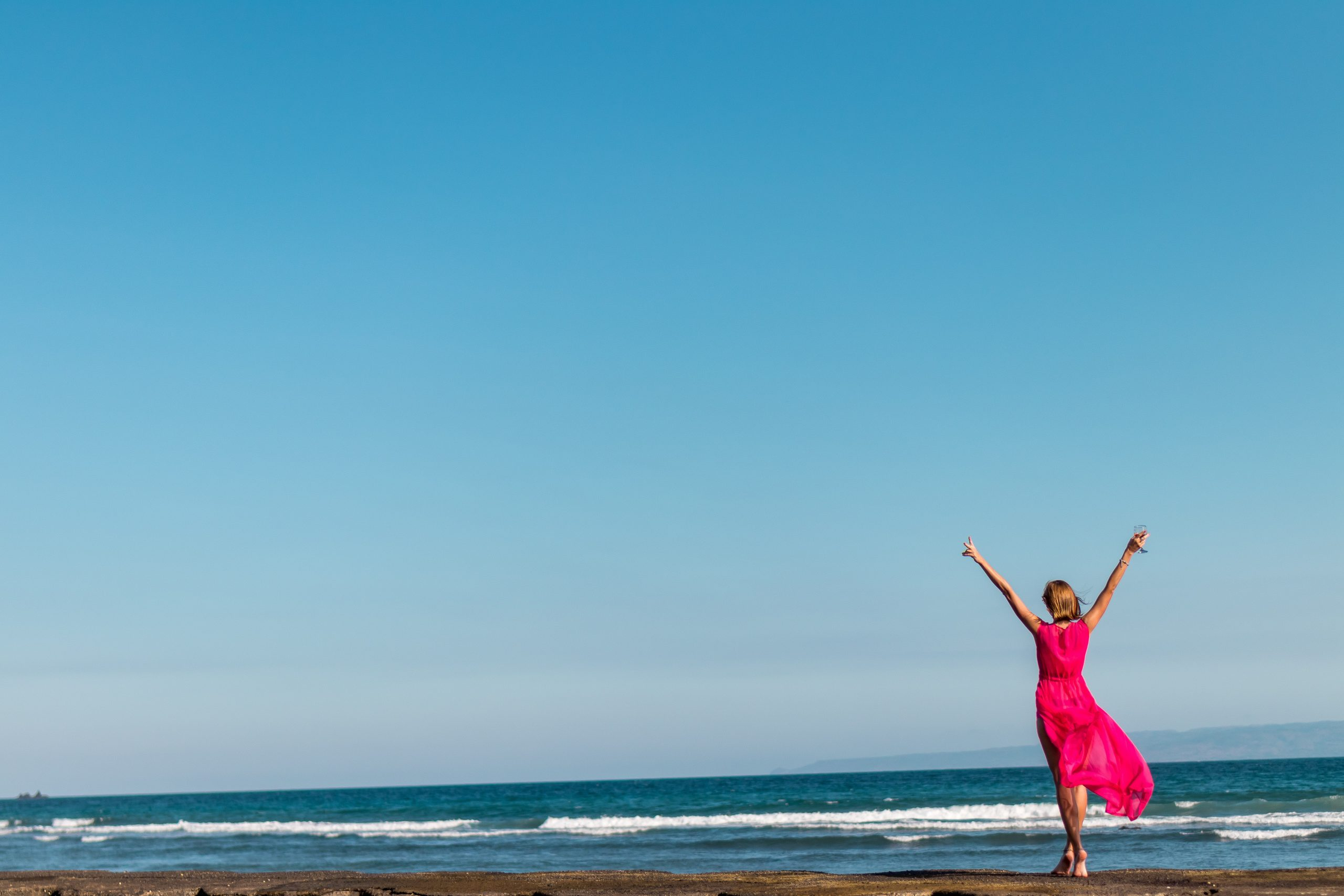 woman-wearing-pink-dress-standing-on-shore-2316088